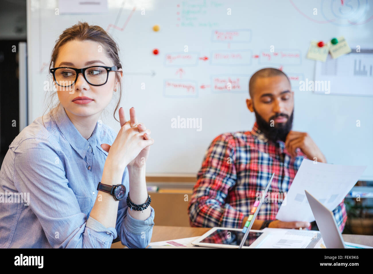 Pensive young woman in glasses sitting in conference room and thinking while her male colleague reading - Stock Image