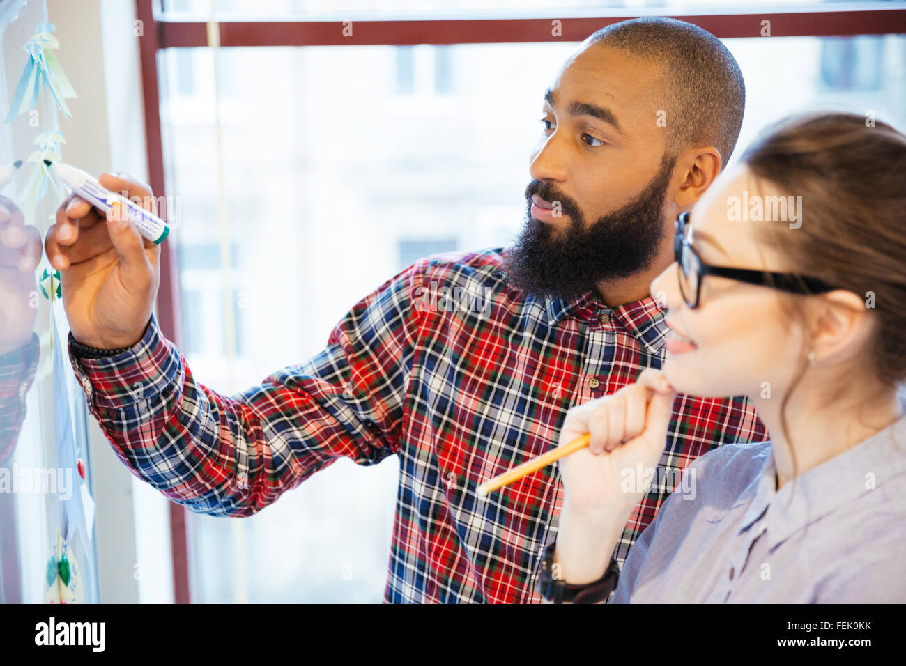 Young business people discussing of something in office - Stock Image