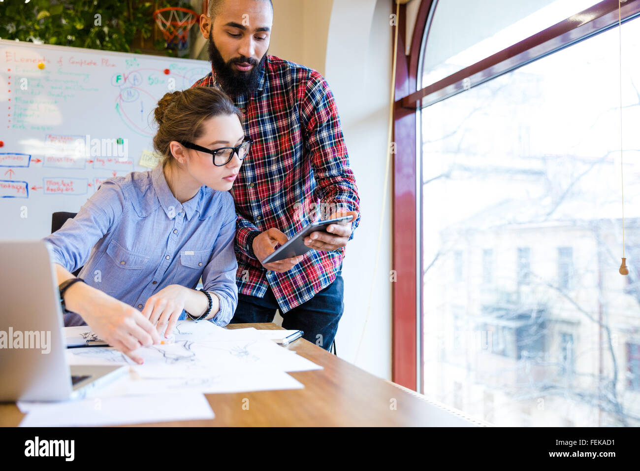 Two young woman and man fashion designers working and using tablet together - Stock Image