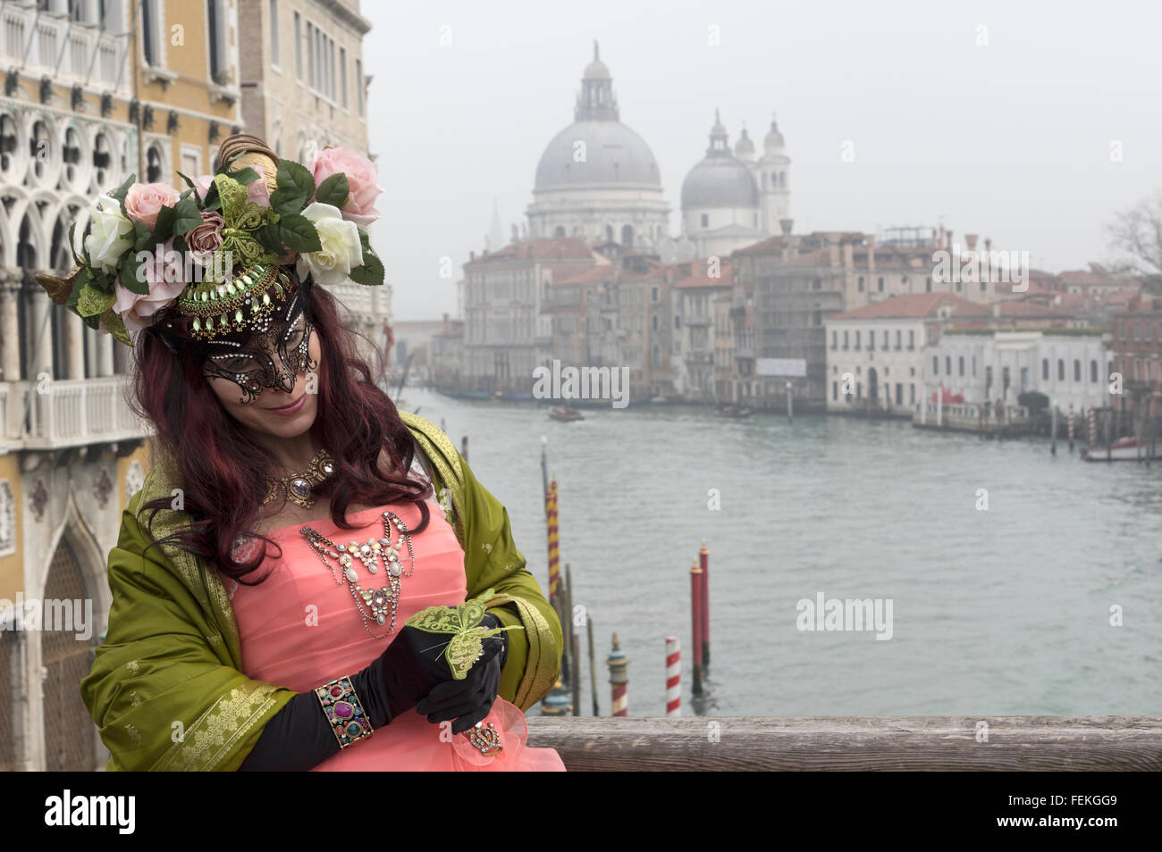 A masked venetian on the academia bridge in Venice with the grand canal and Santa Maria della salute in the background - Stock Image