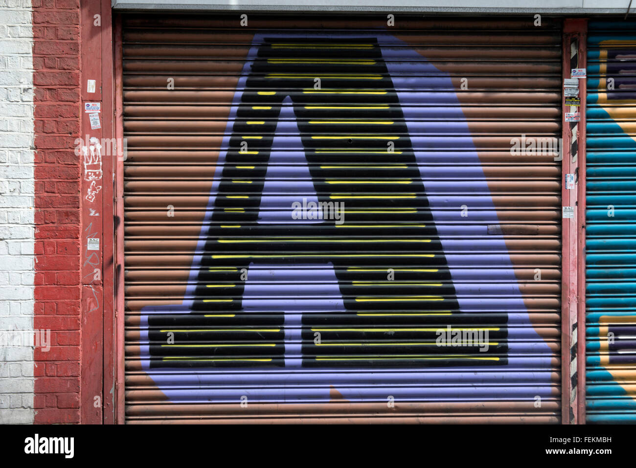 Ben Eine. Street art, a large initial A painted on metal scrolling shutters. - Stock Image