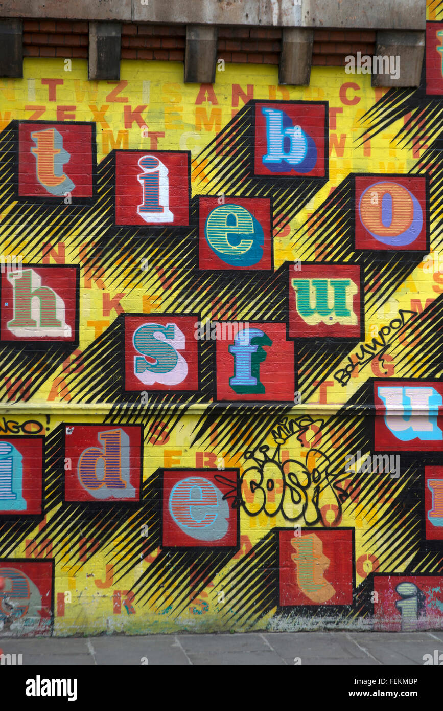Ben Eine. Street art large initials letters painted on metal scrolling shutters. Multicoloured. - Stock Image