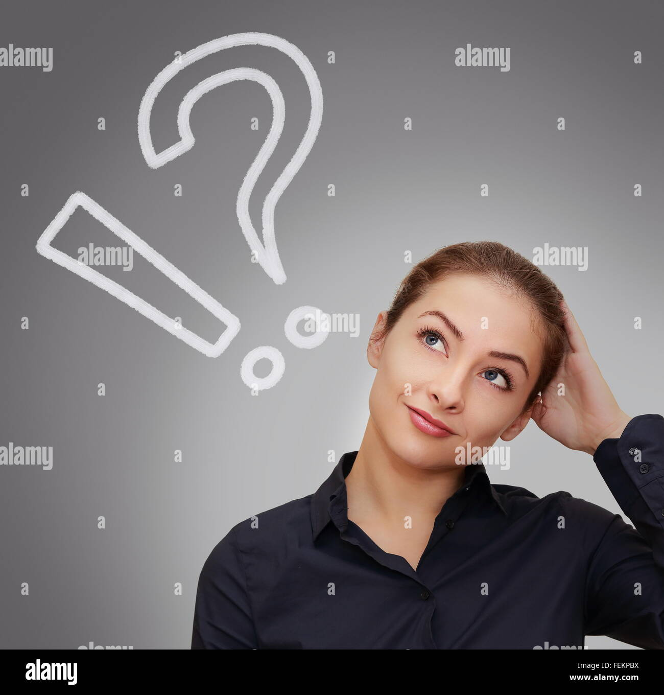 Thinking woman with question and exclamation marks above head on grey background - Stock Image