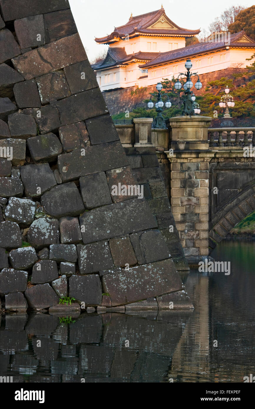 Dawn's first sunlight warmly illuminates an elegantly angled corner of the inner moat's stone wall Nijubashi - Stock Image