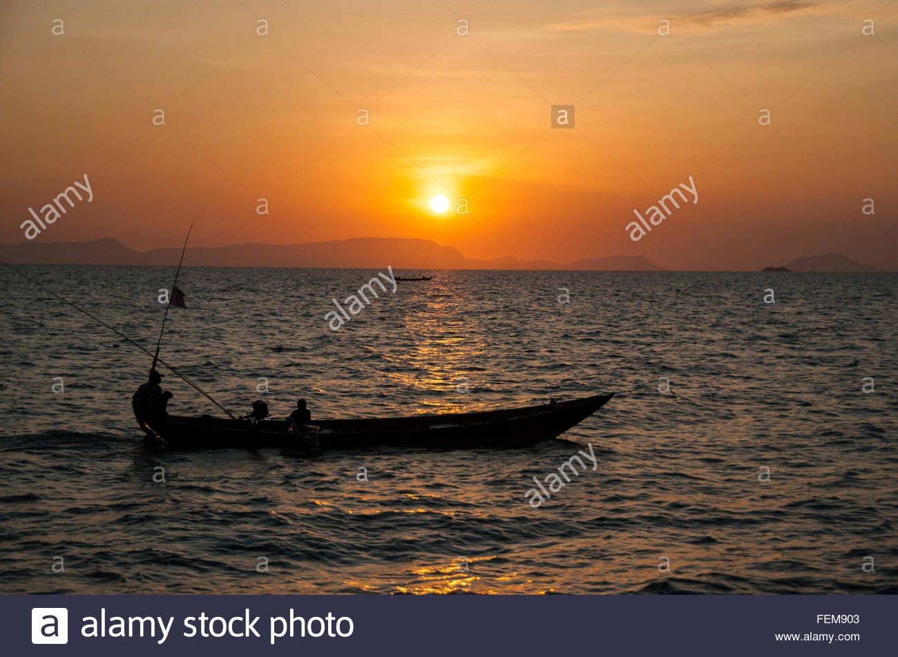 Two fishing boats silhouetted against the setting sun in the Gulf of Thailand off Kep, Cambodia, SE Asia Stock Photo