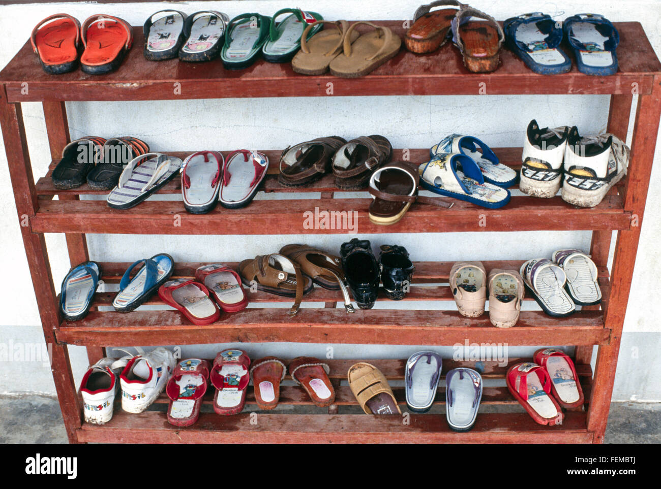 Finest Young school children's tiny shoes on a wooden shoe rack outside a  OK04