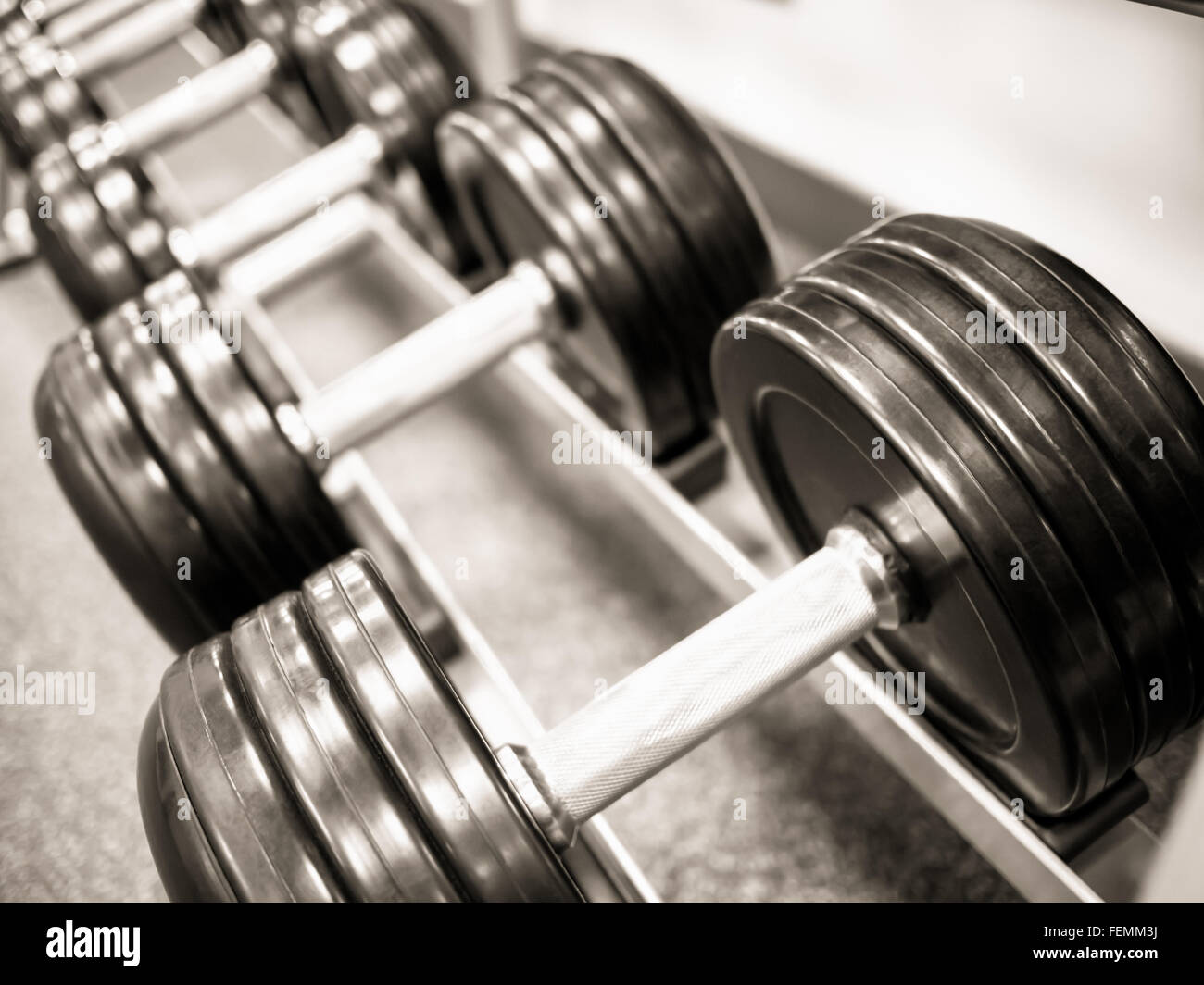 Dumbbell free weights on a rack at a health club gym - Stock Image