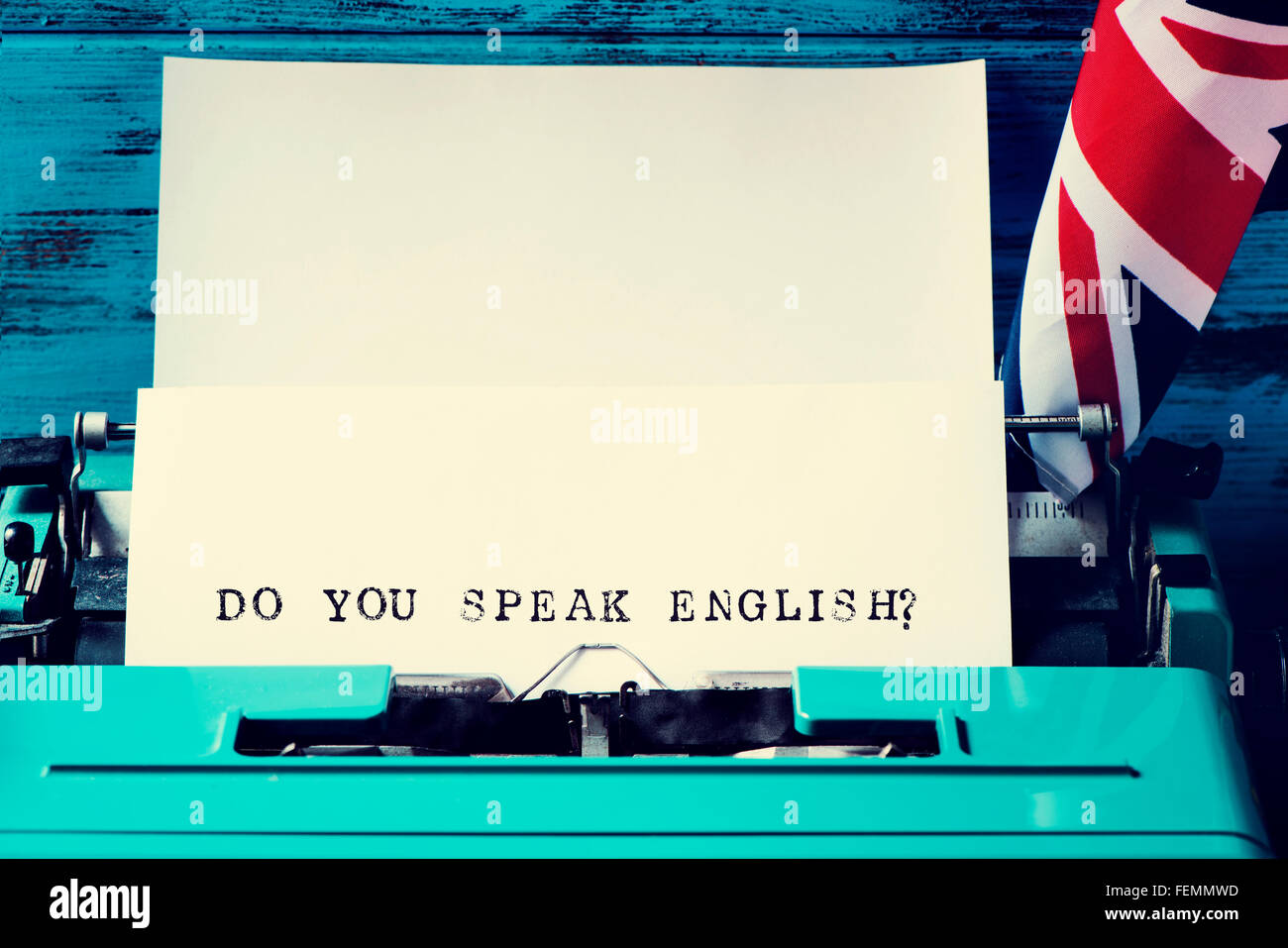 closeup of a paper in an old blue typewriter with the question do you speak english? typewritten in it, and the - Stock Image