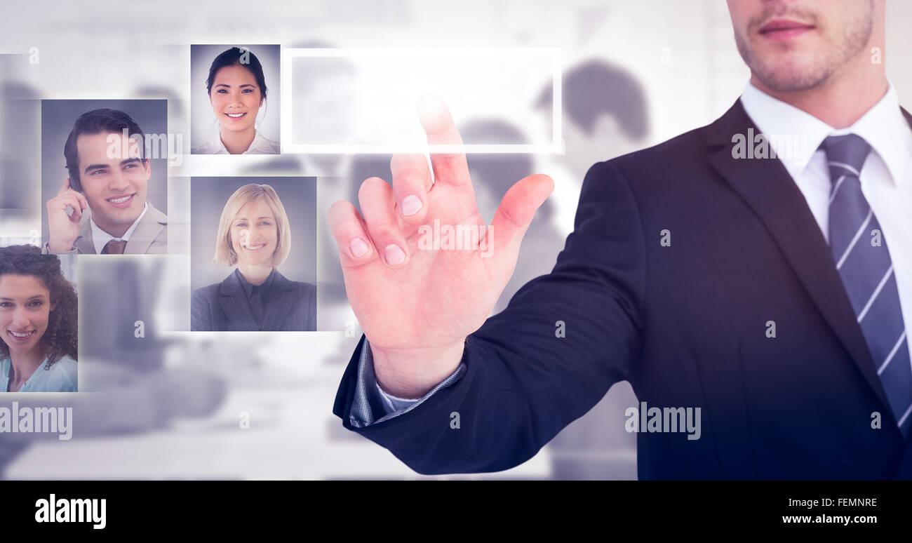 Composite image of focused businessman pointing with his finger - Stock Image