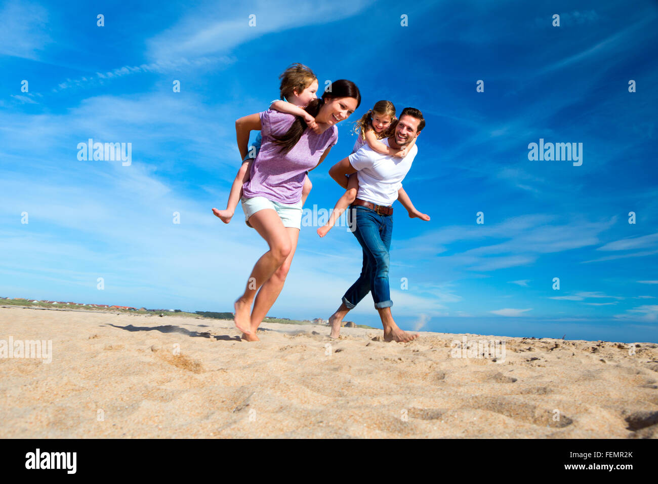Mother and father piggybacking their son and daughter on the beach - Stock Image