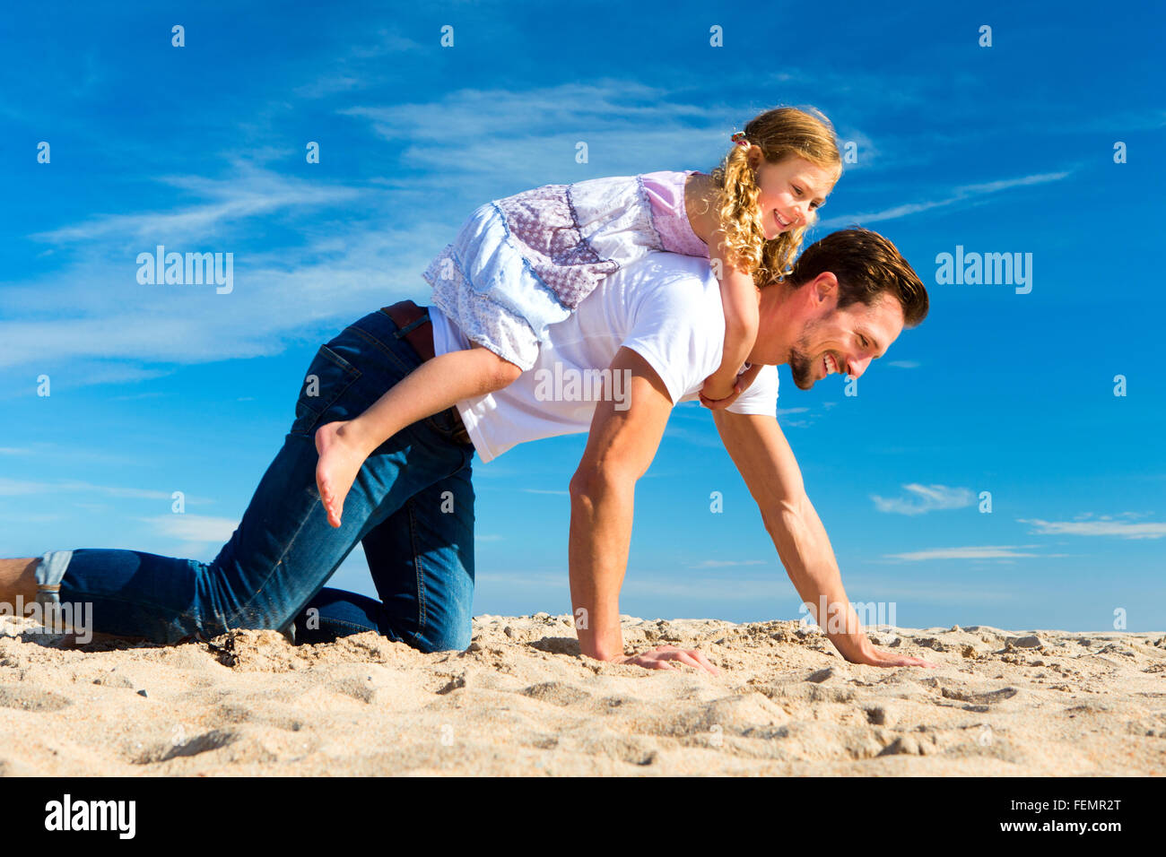 Father carrying his daughter on his back along the sand on the beach. - Stock Image
