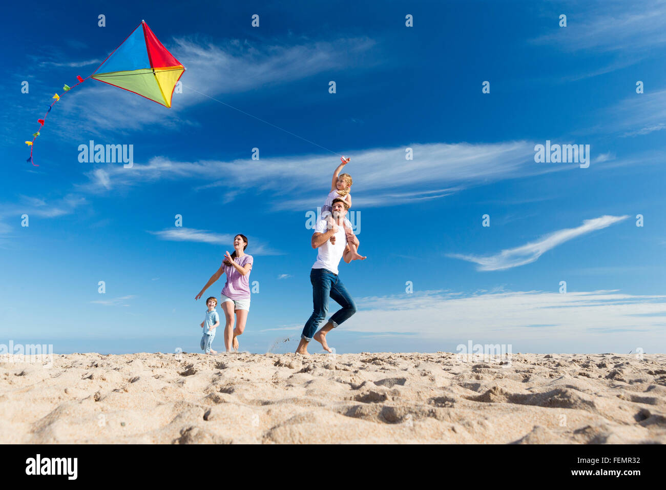 Family of four flying a kite on the beach. - Stock Image