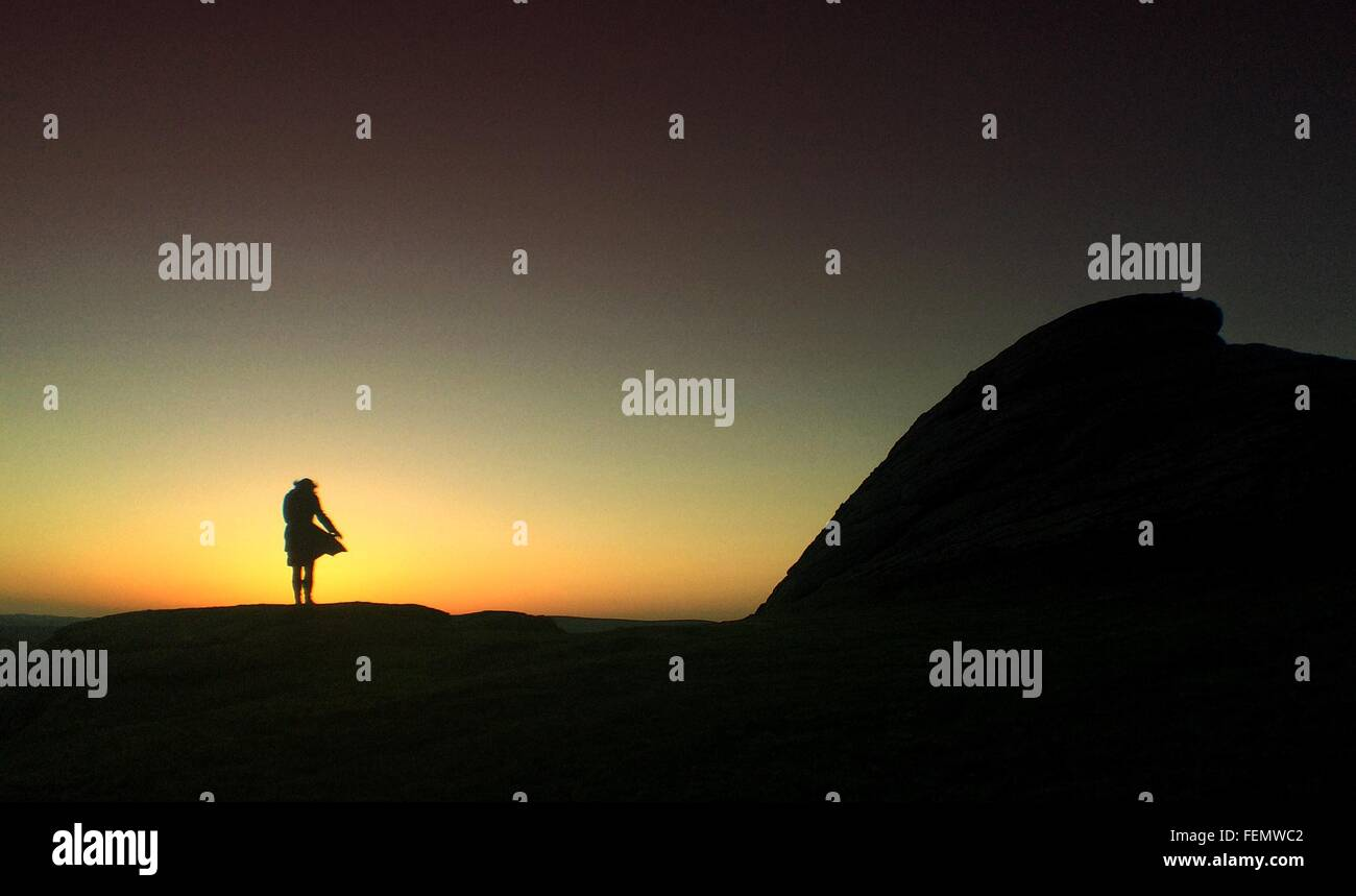 Silhouette Of Woman Standing On Rocks - Stock Image