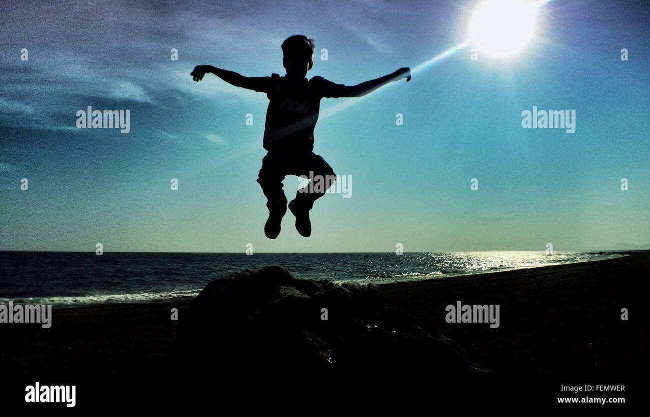 Boy Jumping Into Air Against Sun - Stock Image