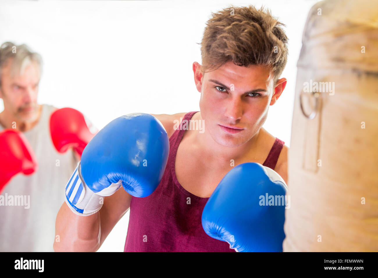 Attractive young man in a boxing stance with gloves and a punching bag - Stock Image