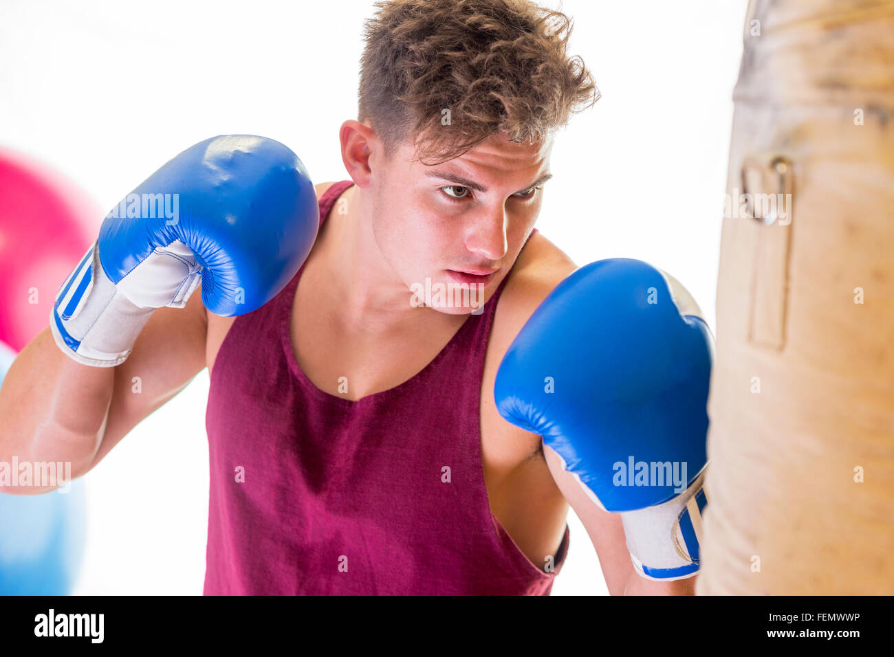Attractive young man in boxing position hitting a punching bag - Stock Image
