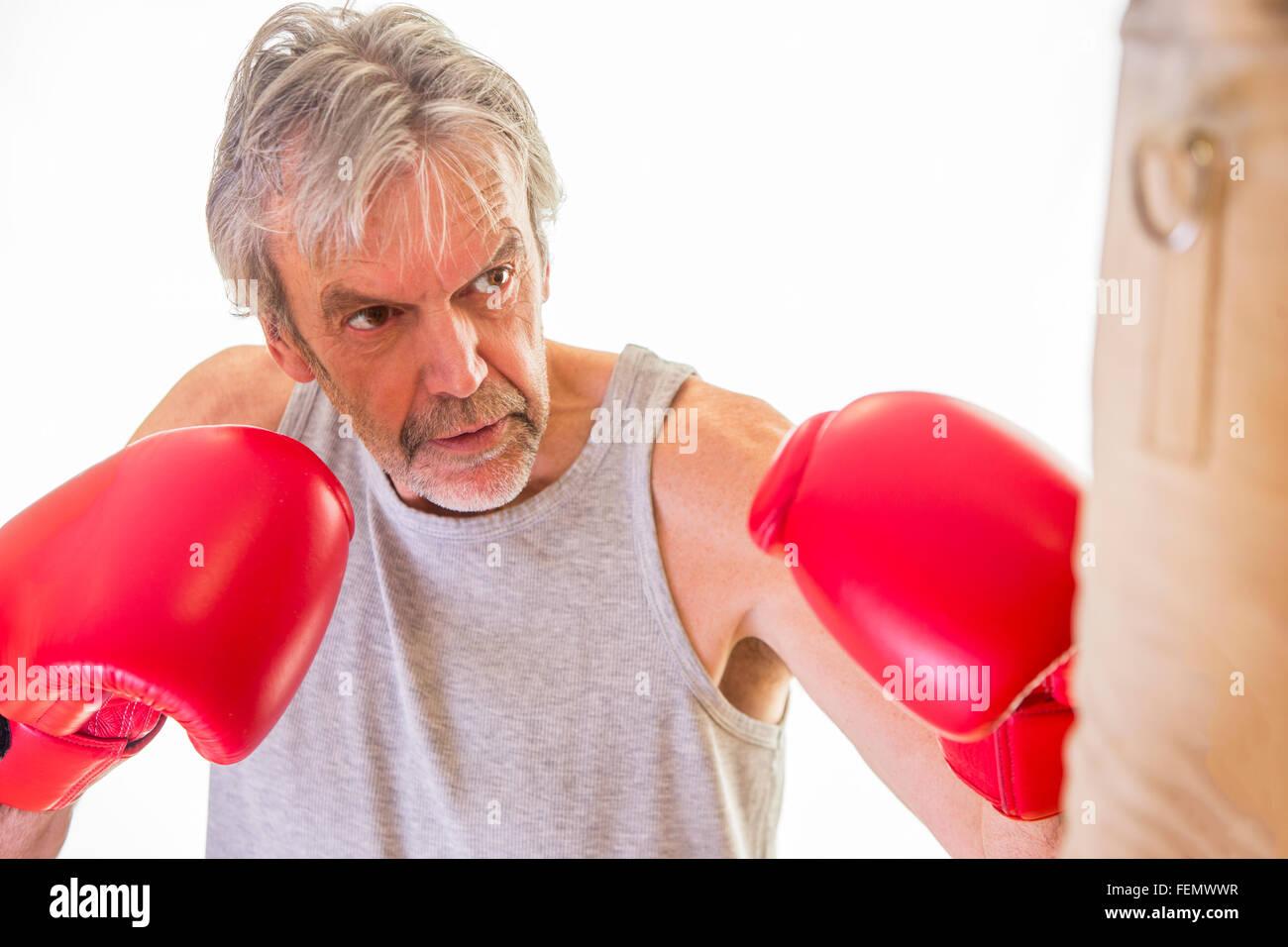 Senior man wearing gloves using a punching bag - Stock Image