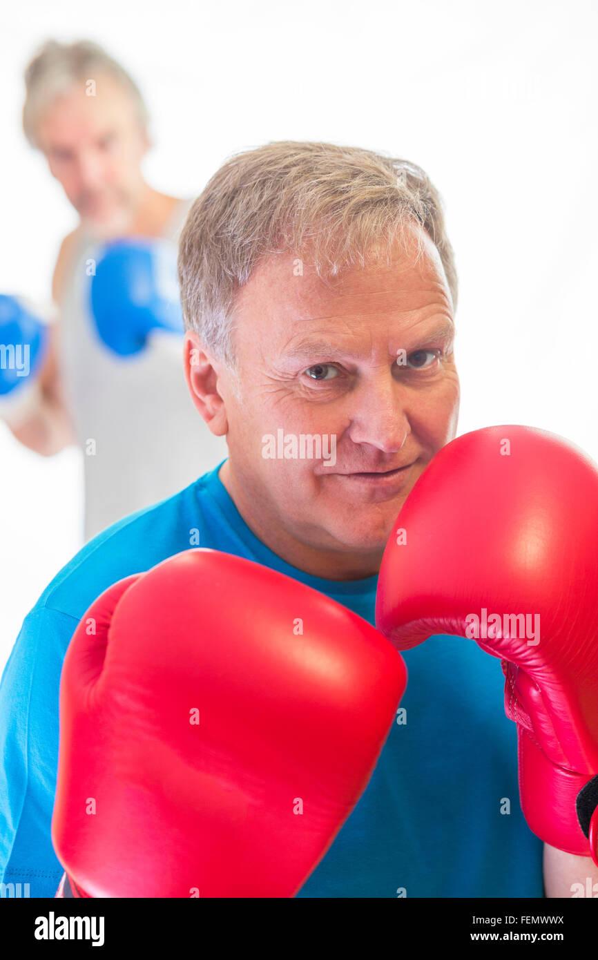 Senior man posing in a boxing stance wearing gloves - Stock Image