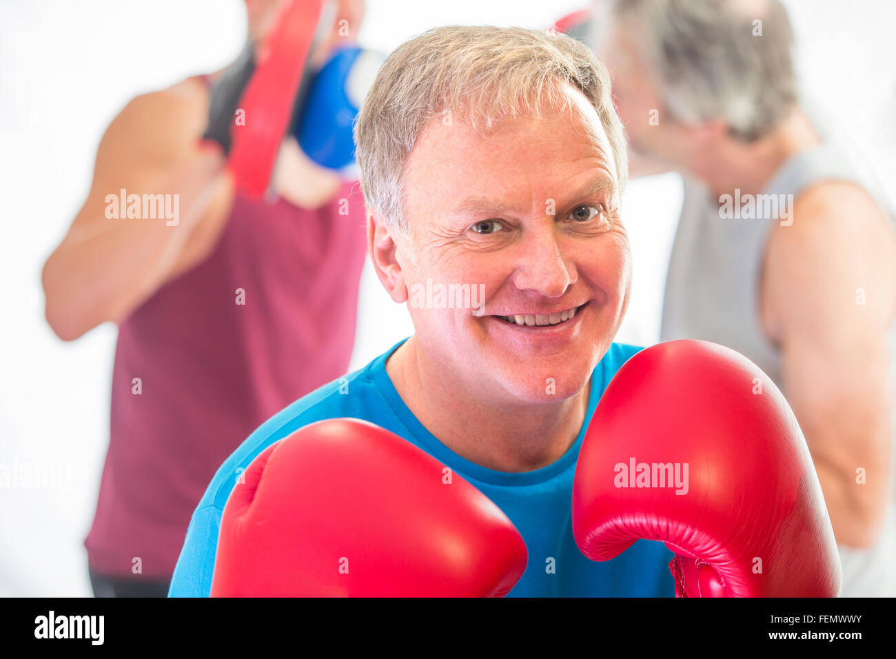 Senior man posing posing in a fighting stance with boxing gloves - Stock Image
