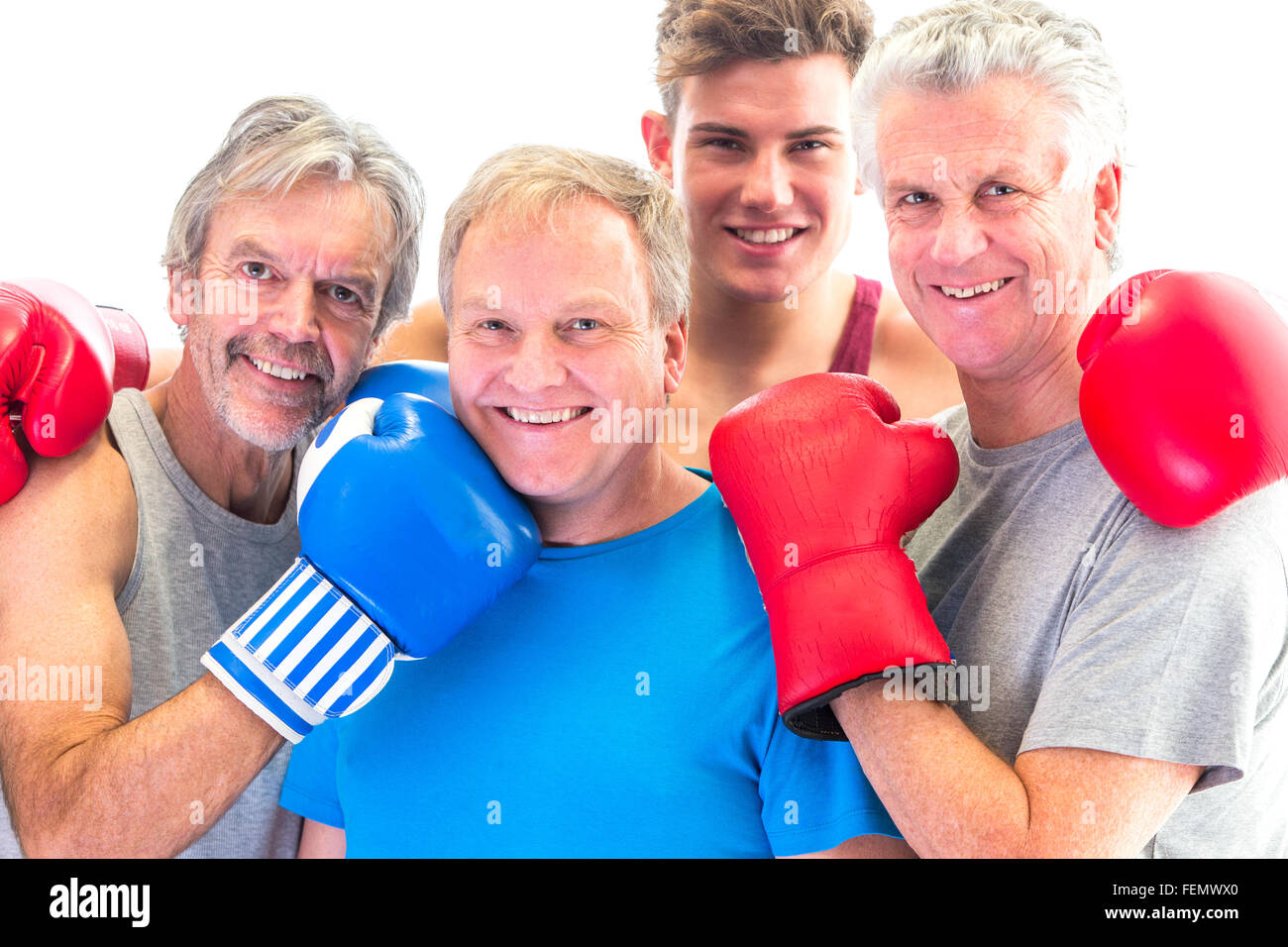 Three senior men in gloves posing with their trainer - Stock Image