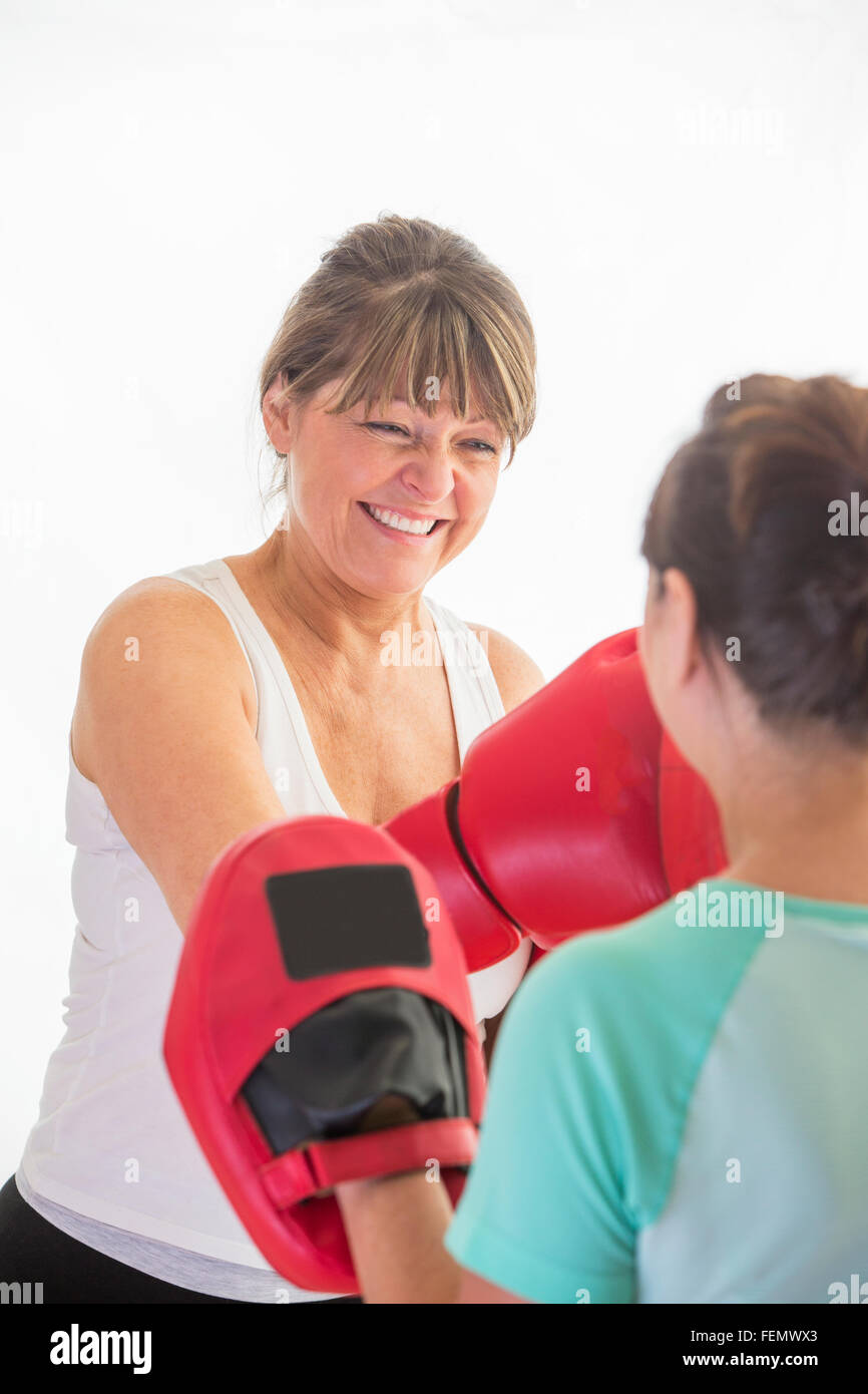 Senior woman training with boxing gloves - Stock Image