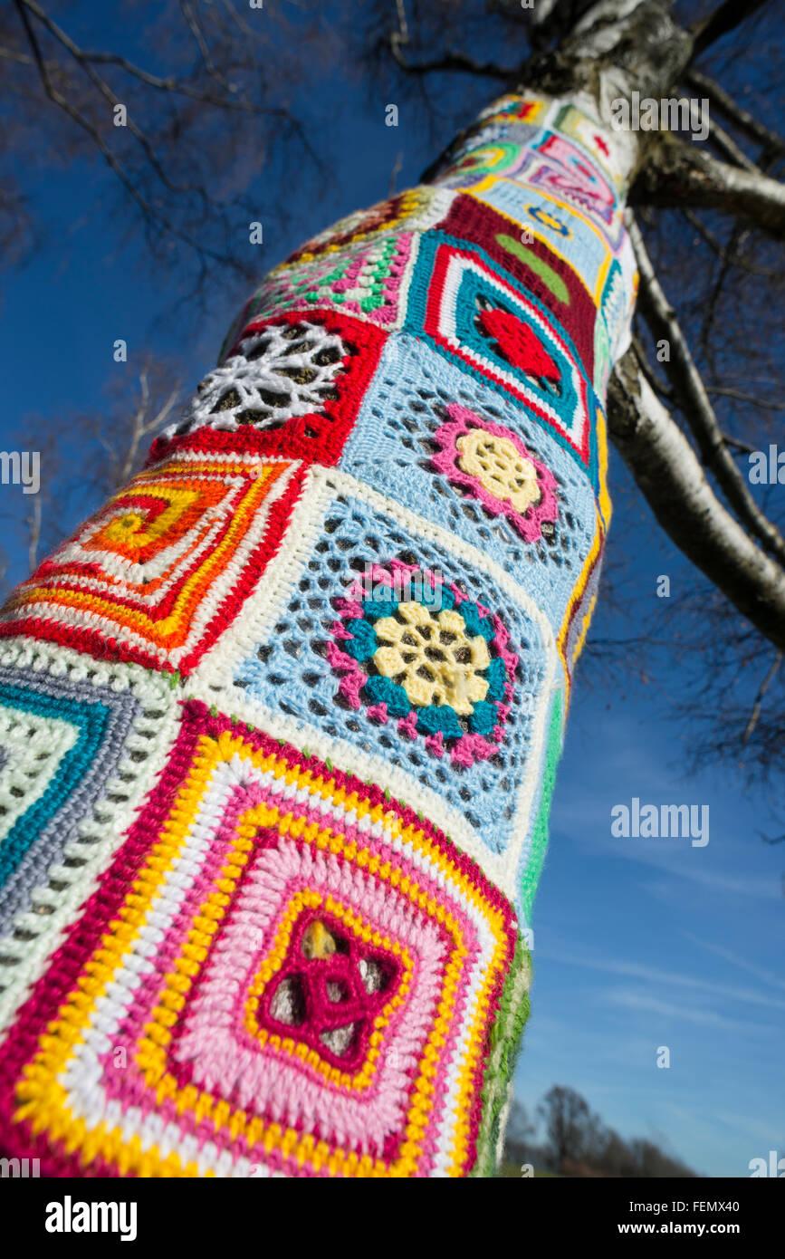 Guerilla knitting - closeup of colorful wool patterns around a tree ...