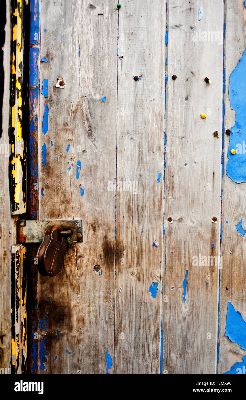 Yellow and Blue distressed paint on wooden door - Stock Image