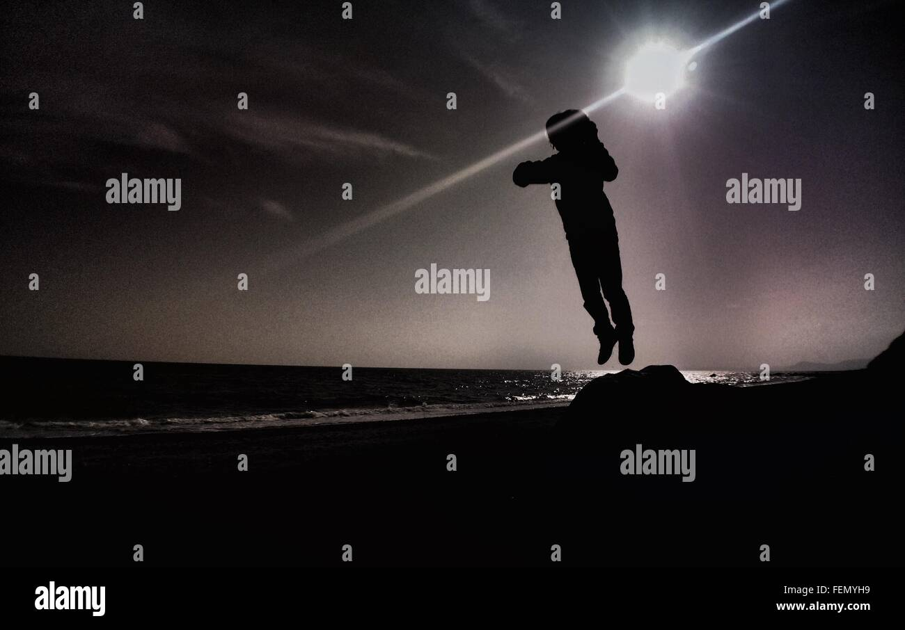 Person Leaping Into Air Against Sun - Stock Image