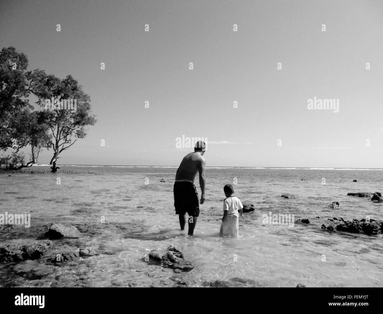 Man With His Son Walking On Beach Stock Photo