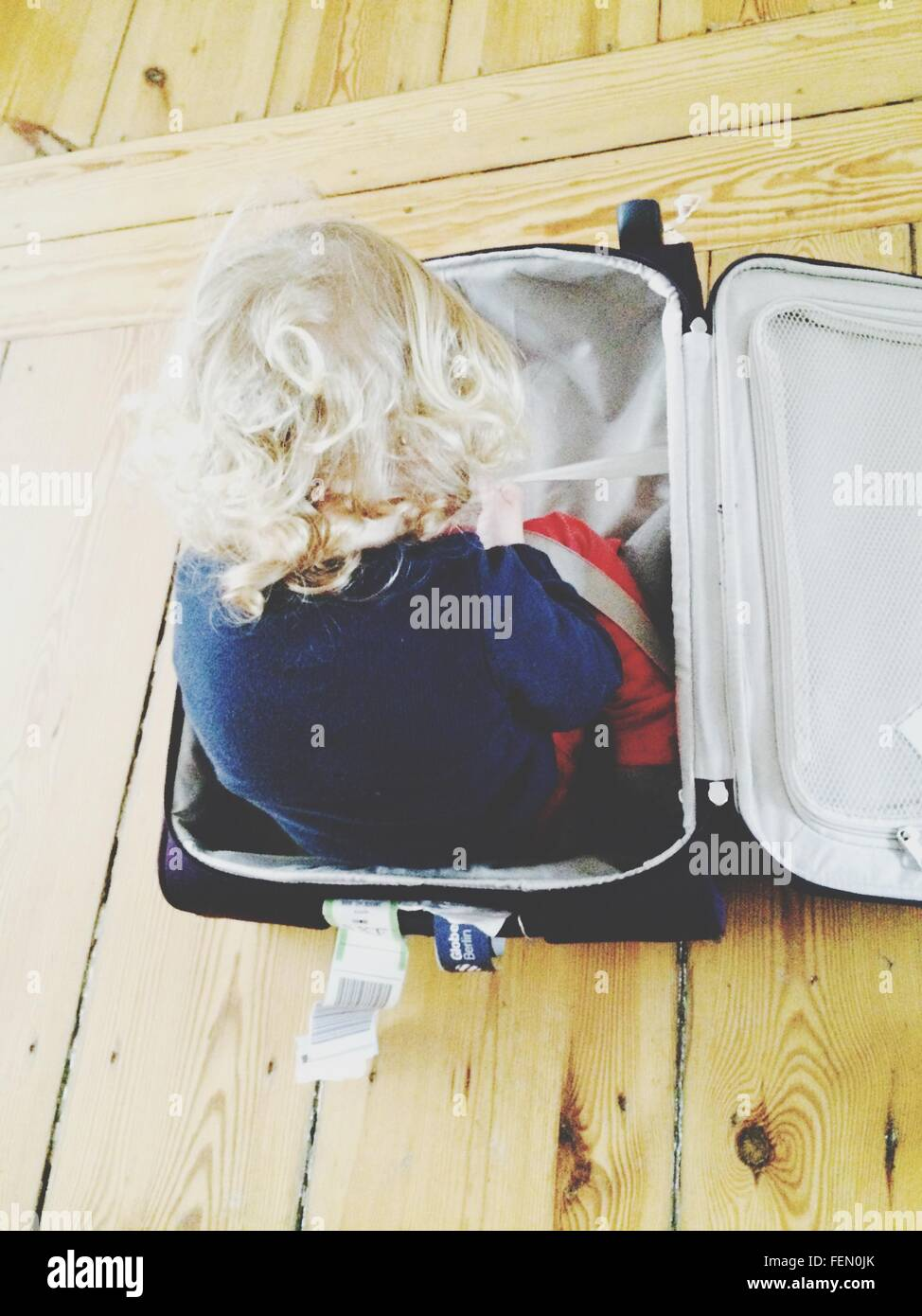 Rear View Of Girl In Suitcase At Home - Stock Image