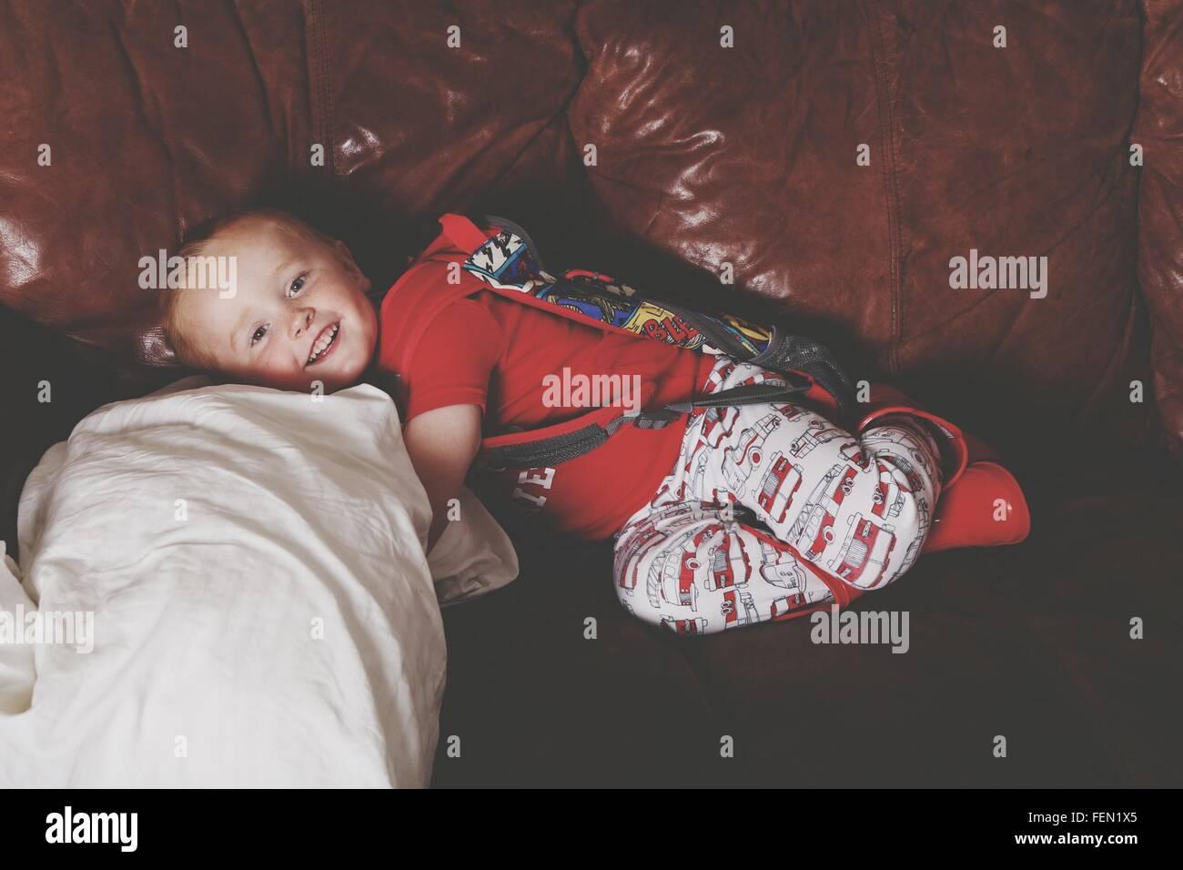 Boy Lying On Sofa And Smiling - Stock Image