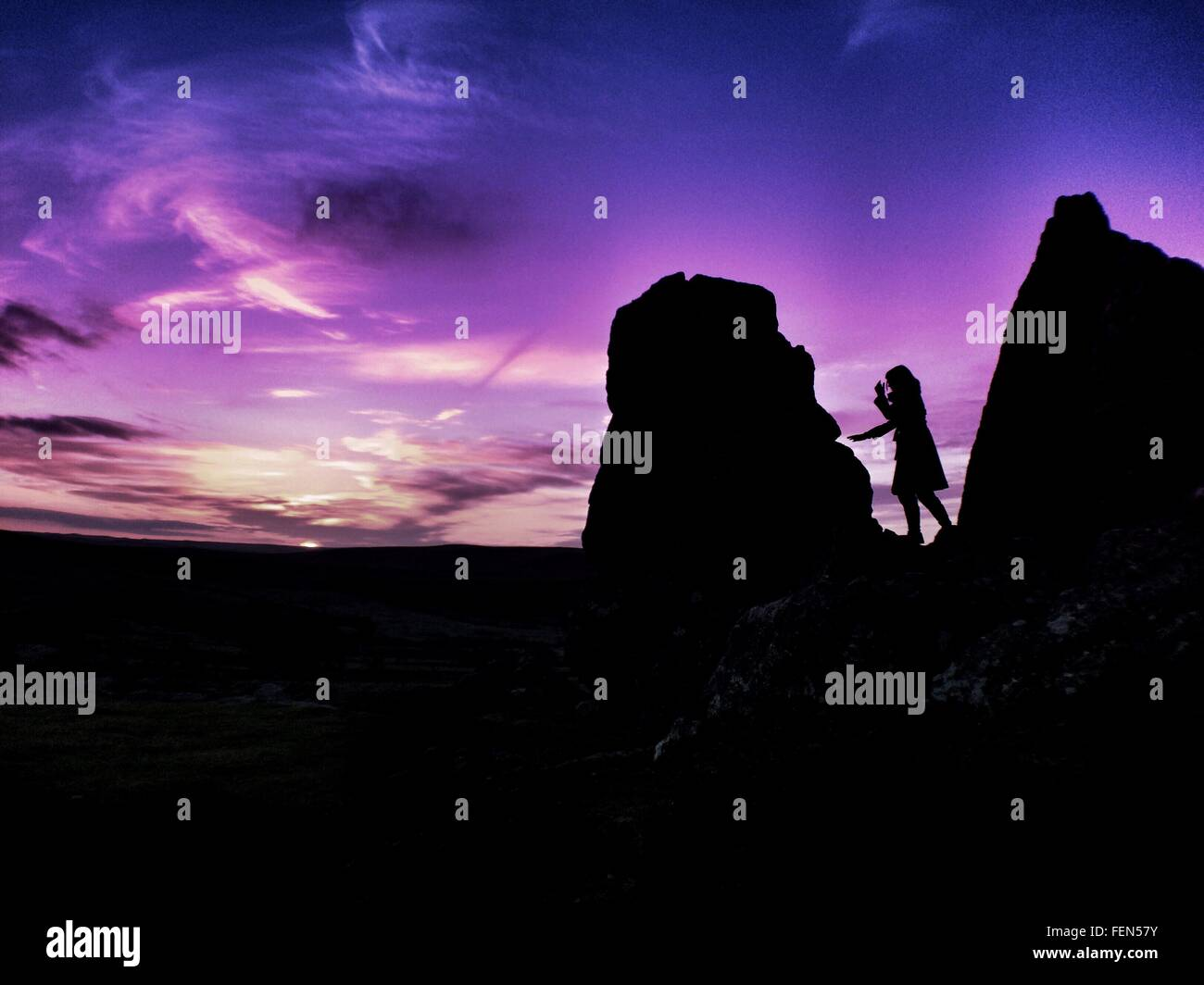 Silhouette Woman On Rocks In Dartmoor National Park At Dusk - Stock Image