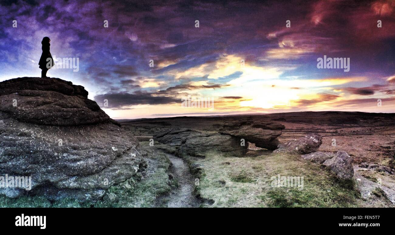Silhouette Woman On Rocks In Dartmoor National Park Against Sky During Sunset - Stock Image