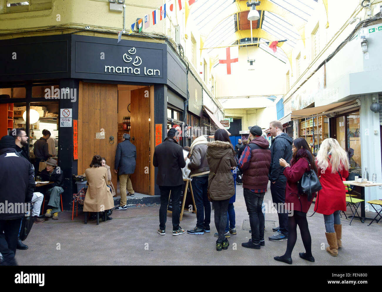 Customers queue outside Mama Lan Chinese restaurant in Brixton Village Market, London - Stock Image
