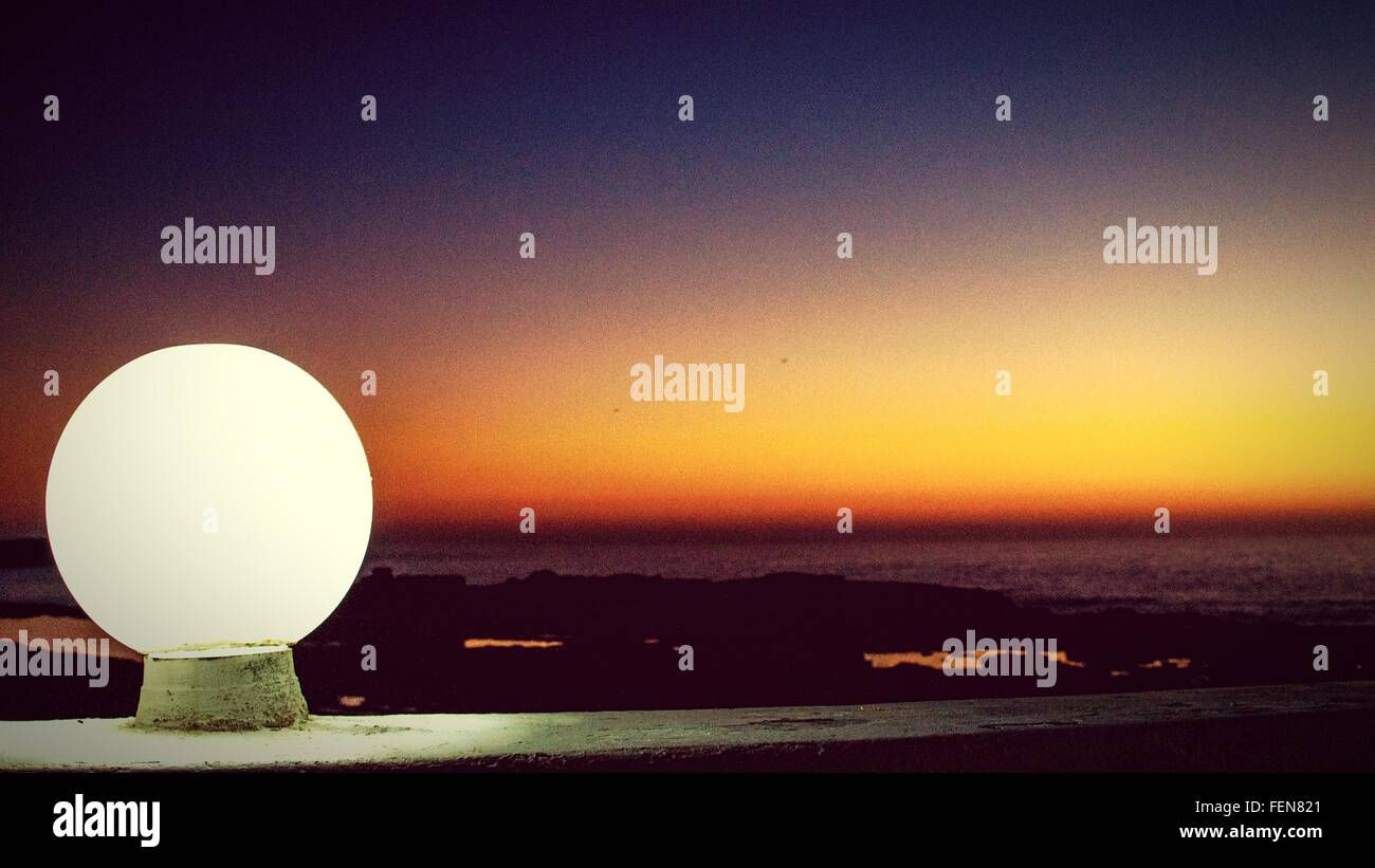 Illuminated Lighting Equipment On Retailing Wall By Sea Against Sky During Sunset - Stock Image
