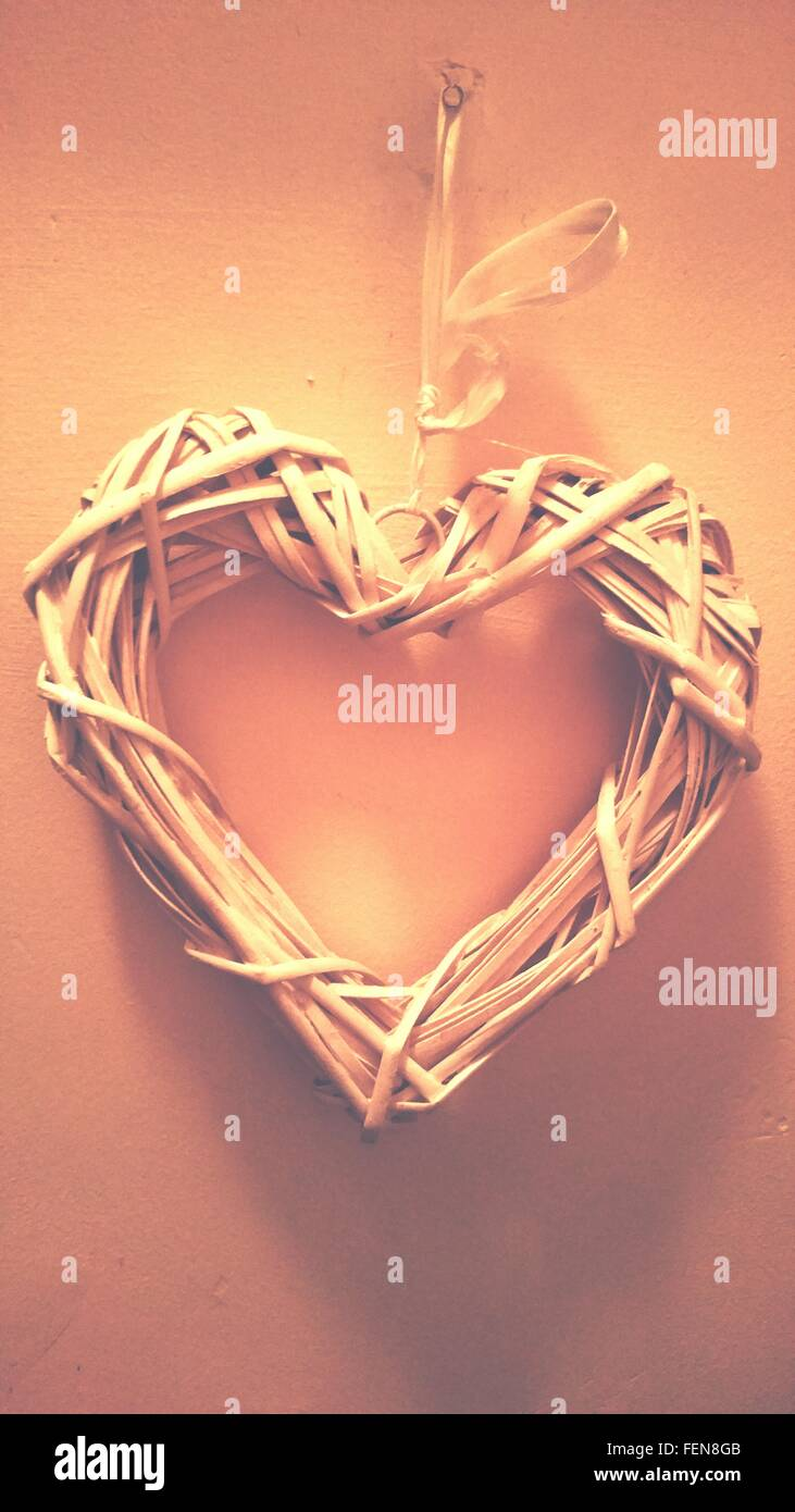 Close-Up Of Heart Shape Wreath Hanging From Wall - Stock Image