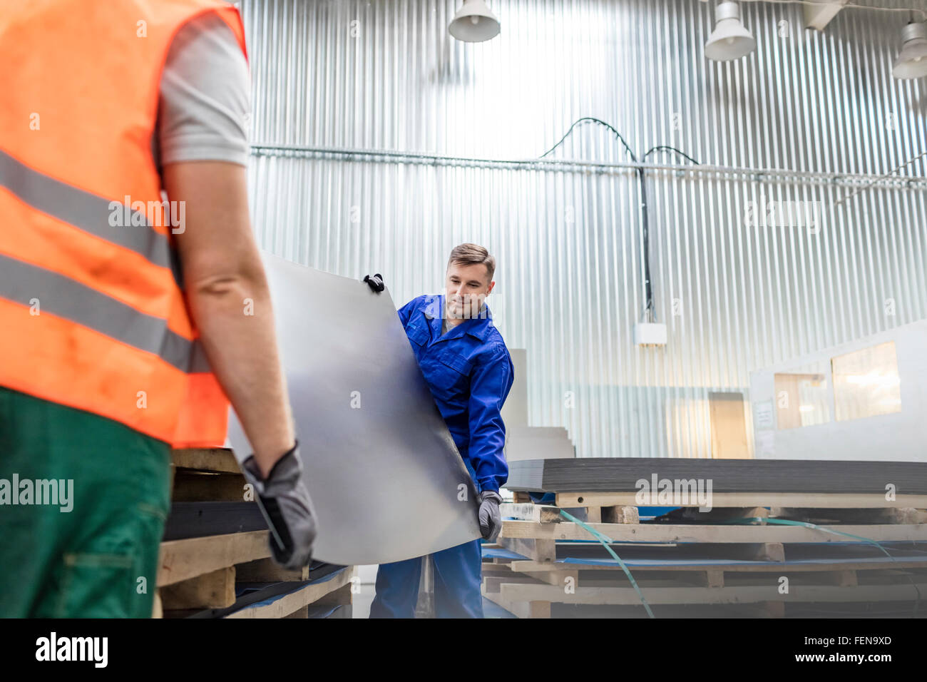 Workers carrying sheet metal in factory - Stock Image