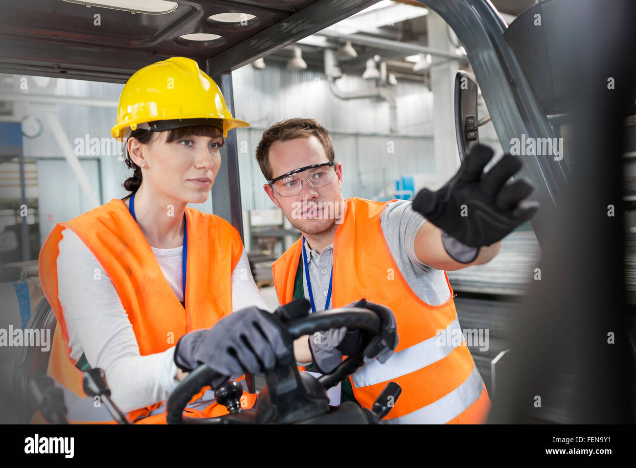 Worker guiding coworker driving forklift in factory Stock Photo