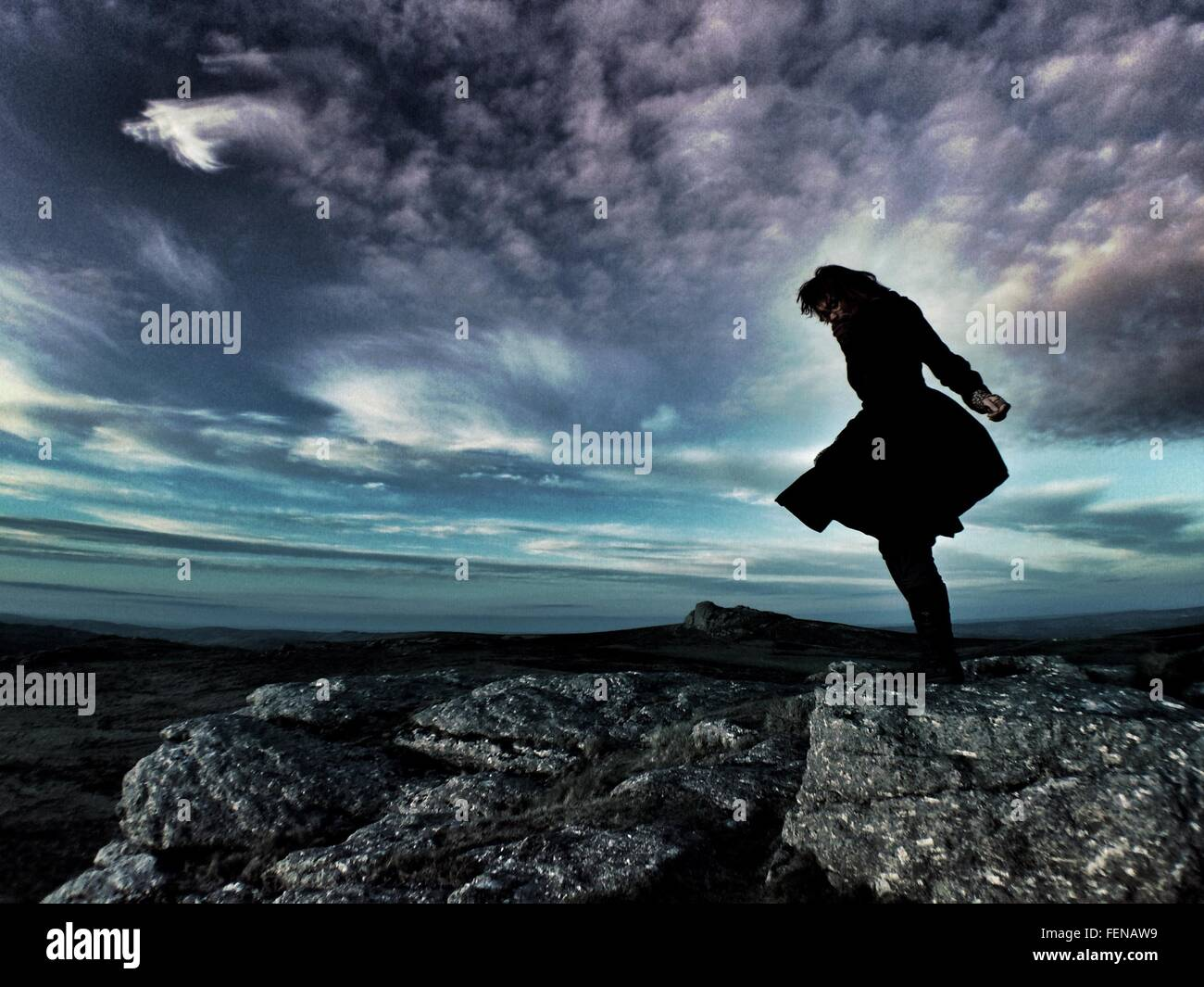 Silhouette Woman Standing On Rock Against Cloudy Sky - Stock Image