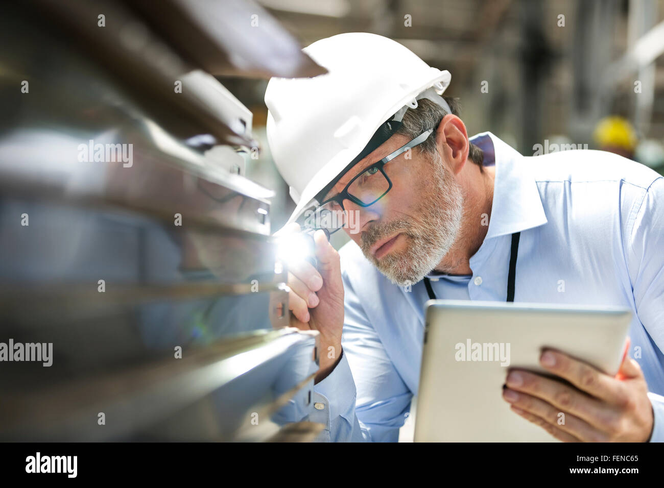 Focused engineer with digital tablet and flashlight examining part in factory - Stock Image