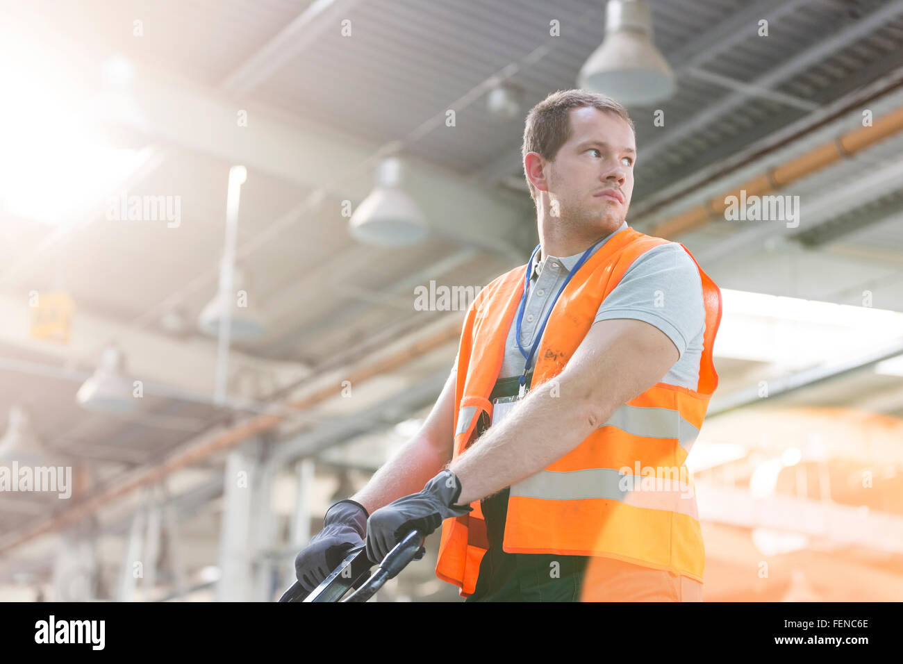 Worker in protective workwear pulling pallet truck in factory - Stock Image