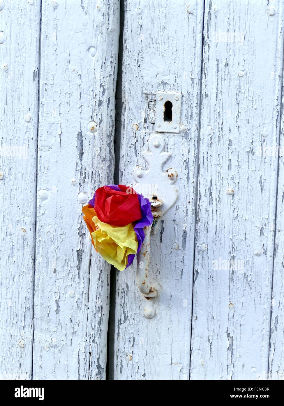 Multi Colored Artificial Flowers On Handle Of White Door - Stock Image