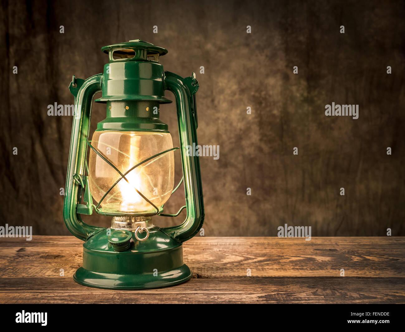 Vintage oil lamp lit on wooden table over dark background - Stock Image