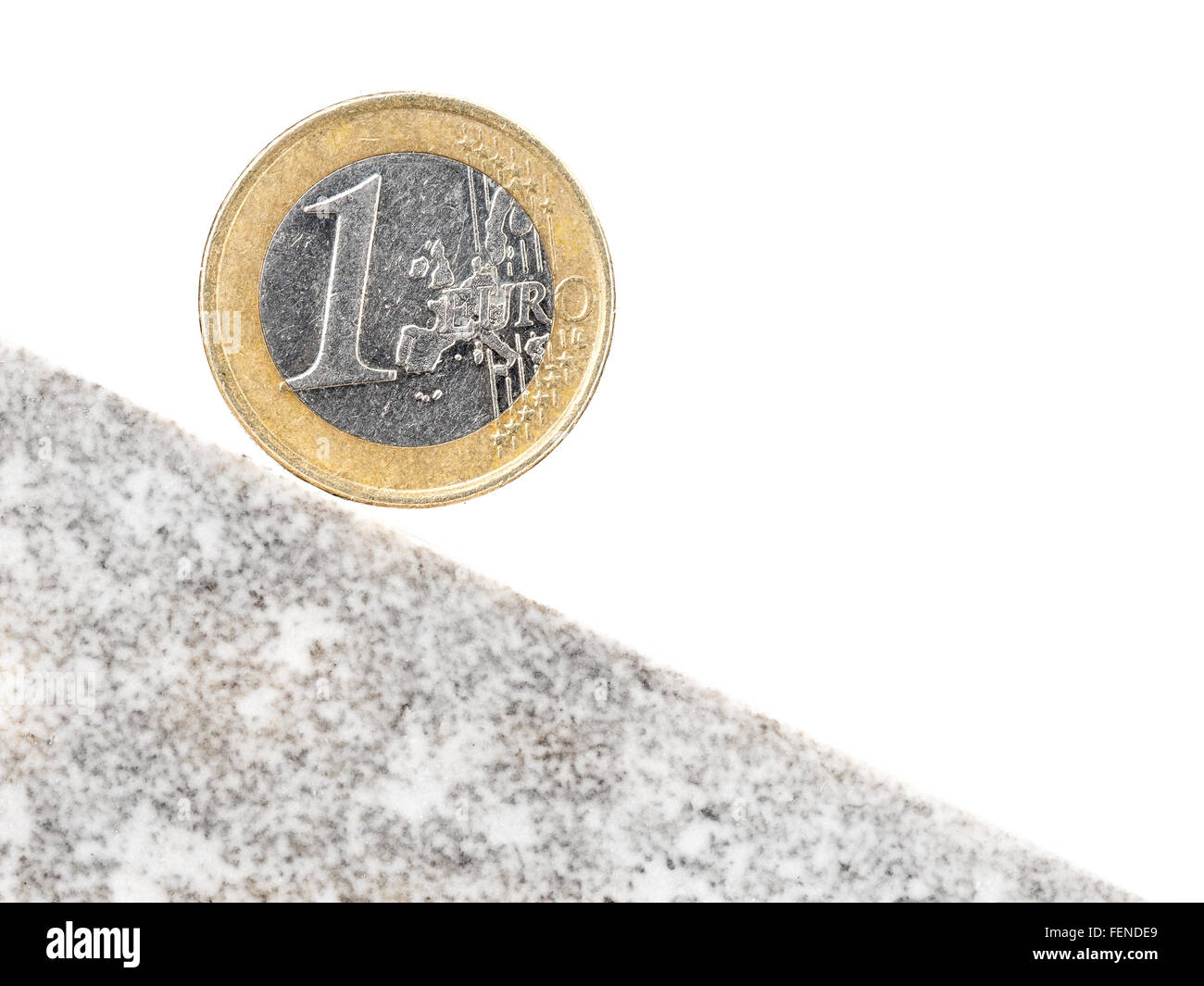 One Euro coin on inclined plane as a metaphor of currency crash - Stock Image