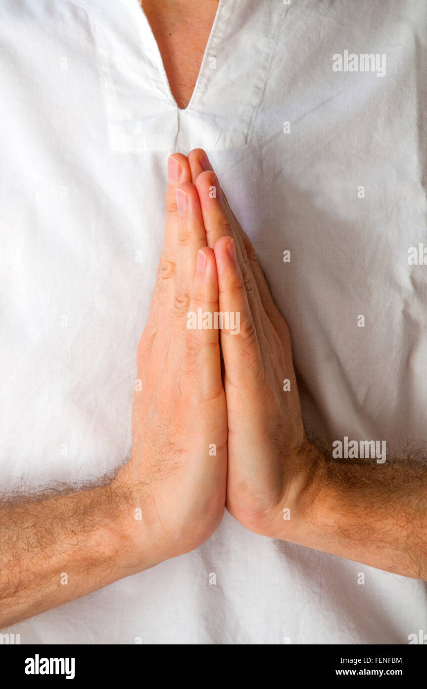 Man practicing yoga, hands in the prayer position. - Stock Image