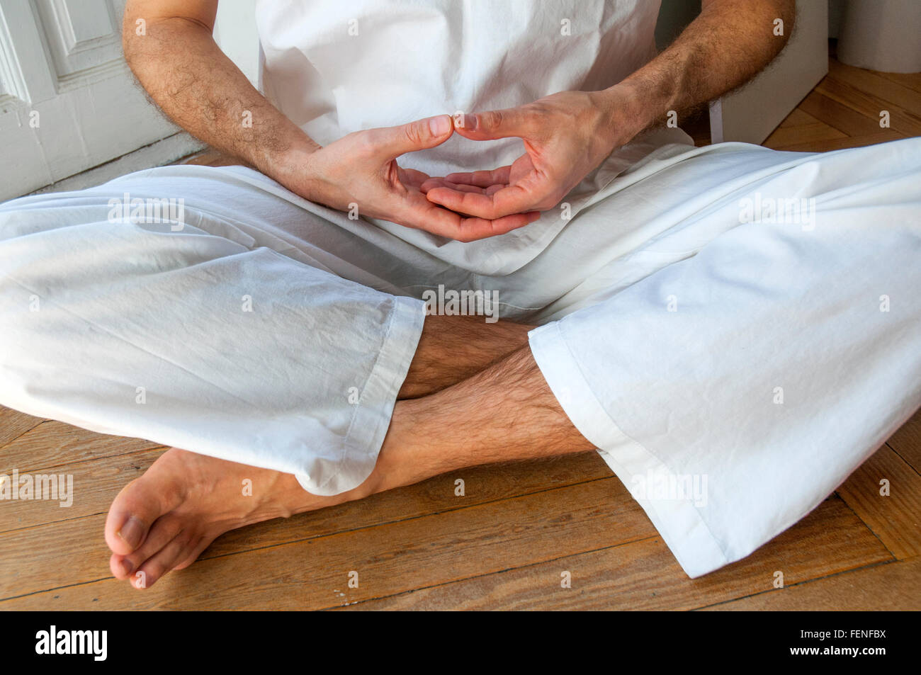 Man practicing yoga, sitting in the lotus position. - Stock Image