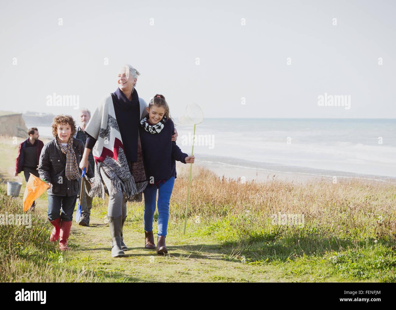 Multi-generation family walking on grassy beach path Stock Photo