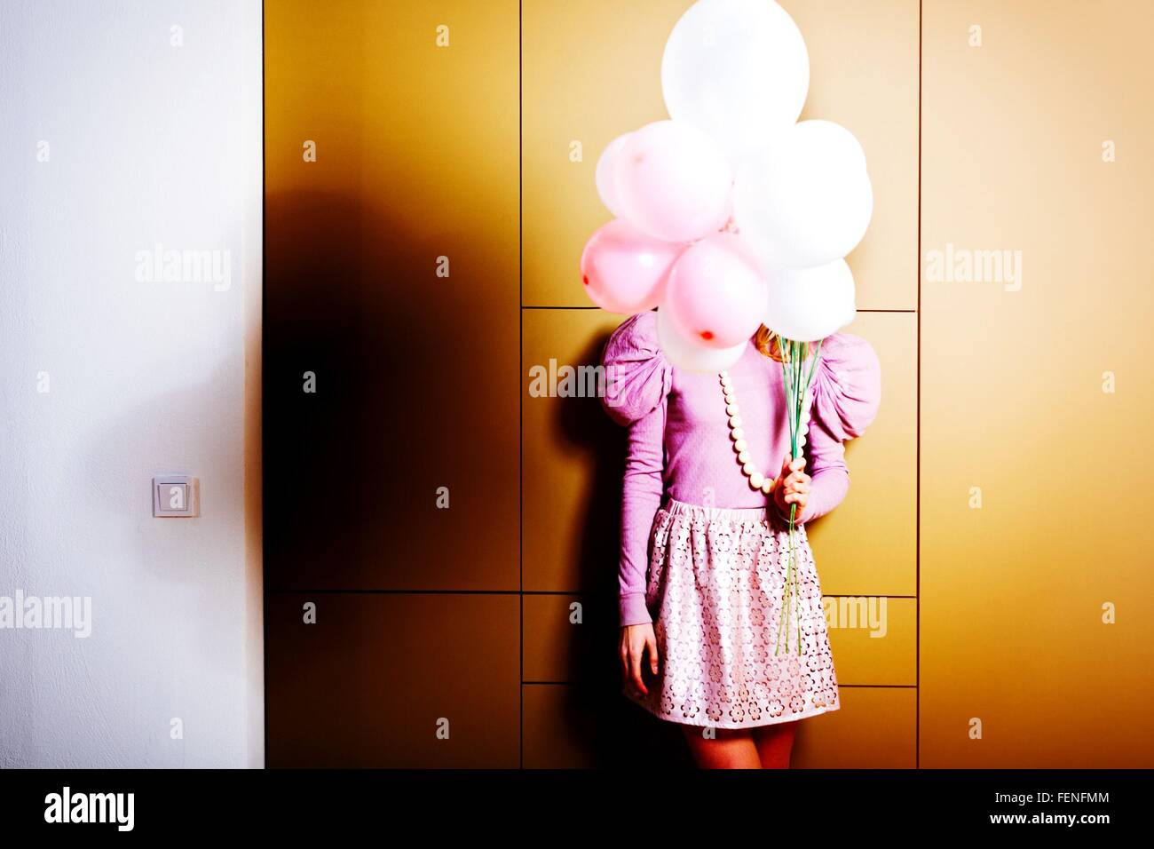 Woman Holding Balloons In Front Of Her Face - Stock Image