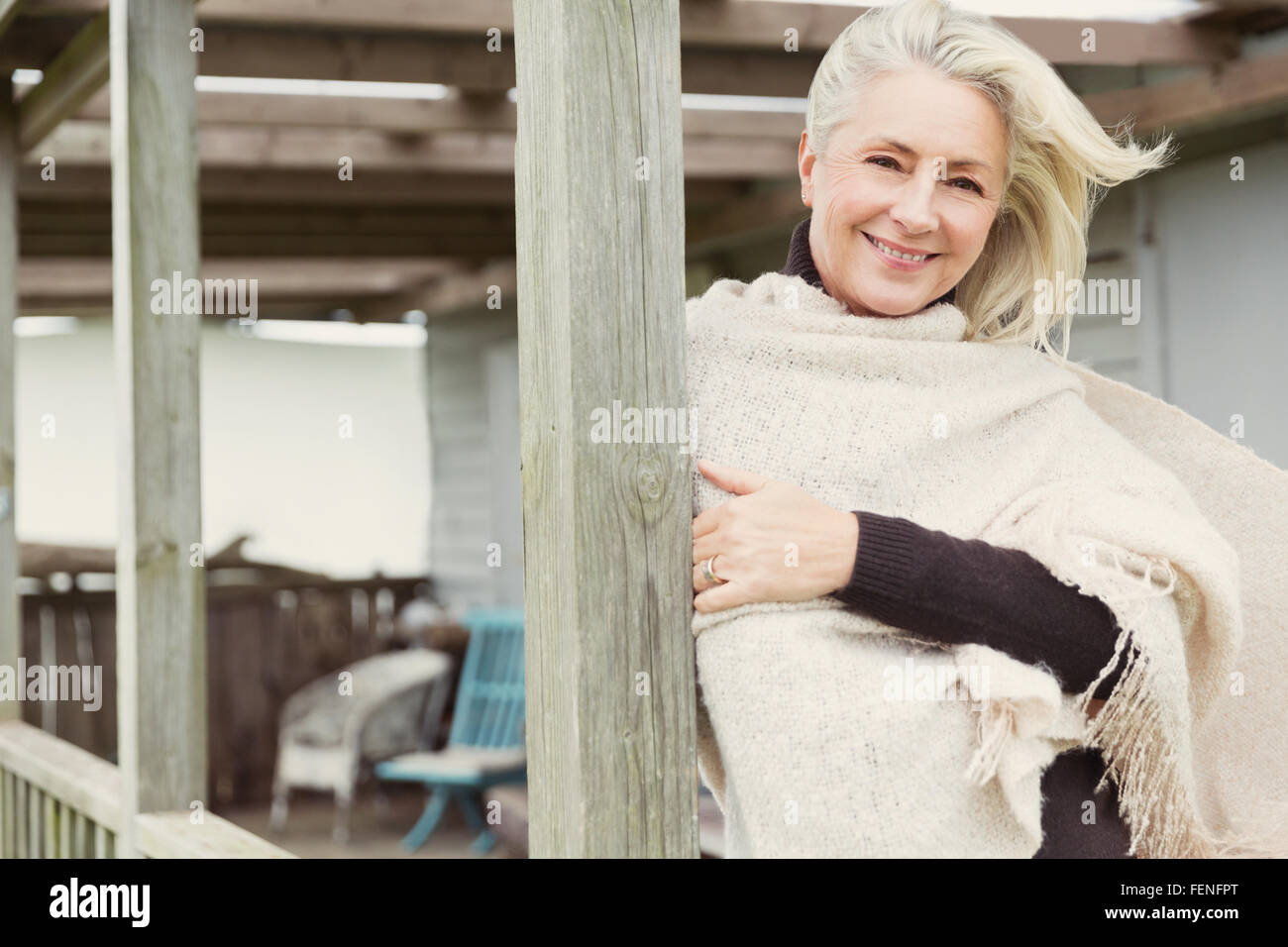 Portrait smiling senior woman wearing shawl on windy porch - Stock Image