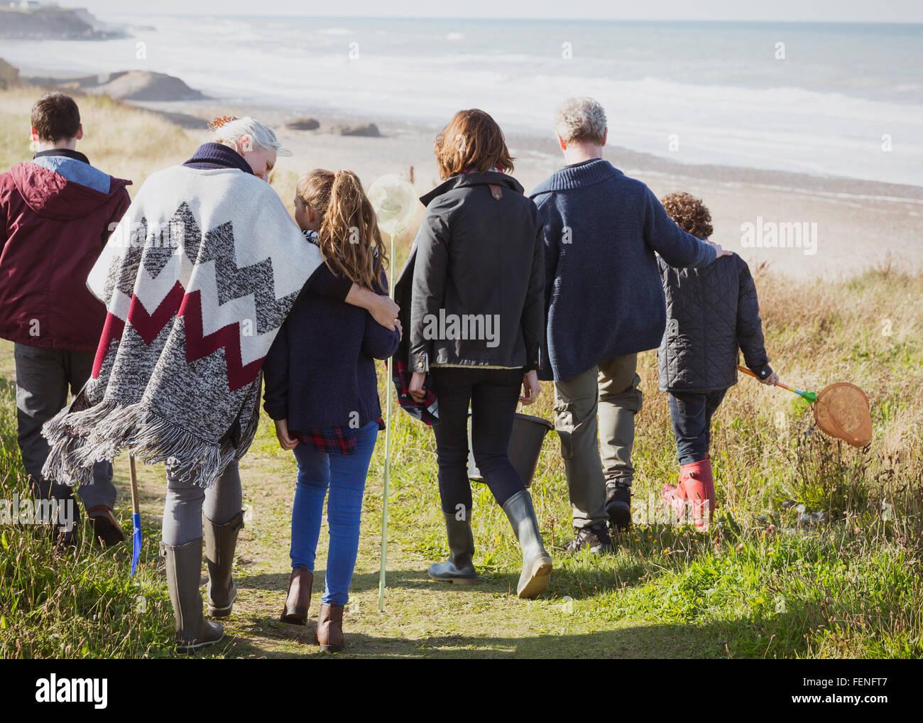 Multi-generation family walking on sunny grass beach path Stock Photo
